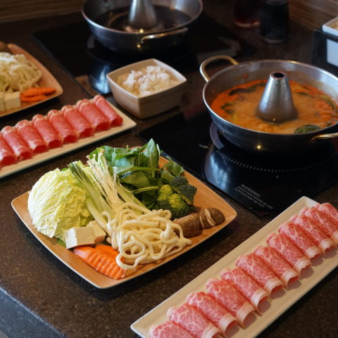 hot pot with thinly sliced meats, mixed vegetable plates